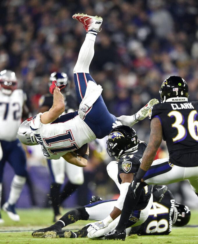 New England Patriots wide receiver Julian Edelman (11) is upended as he collides with Baltimore Ravens cornerback Marlon Humphrey (44) during the first half of an NFL football game, Sunday, Nov. 3, 2019, in Baltimore. (AP Photo/Gail Burton)