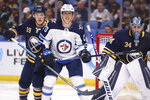 Buffalo Sabres defenseman Jake McCabe (19) and Winnipeg Jets forward Cody Eakin (20) battle for position during the second period of an NHL hockey game Sunday, Feb. 23, 2020, in Buffalo, N.Y. (AP Photo/Jeffrey T. Barnes)