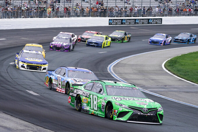 Kyle Busch (18) leads the pack into Turn 1 during a NASCAR Cup Series auto race, Sunday, July 18, 2021, in Loudon, N.H. (AP Photo/Charles Krupa)