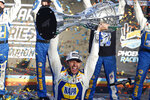 "FILE - Chase Elliott holds up the season championship trophy as he celebrates with his race crew in Victory Lane after winning the NASCAR Cup Series auto race at Phoenix Raceway in Avondale, Ariz., in this Sunday, Nov. 8, 2020, file photo. NASCAR is being heavily promoted by a broadcast partner as about to embark on ""The Best Season Ever"" and on paper that could be true. NASCAR this year will race on dirt for the first time since 1970, the schedule includes a whopping seven road courses and five venues new to the Cup Series. Michael Jordan and Pitbull are among new team owners entering the sport in 2021 and Chase Elliott, NASCAR's most popular driver, is the reigning champion. (AP Photo/Ralph Freso, File)"