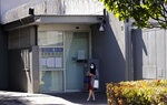 A woman stands in front of the Chinese consulate in Sydney, Wednesday, Sept. 16, 2020. A Chinese-born adviser to an Australian lawmaker has launched a constitutional challenge in Australia's highest court against the nation's laws that ban covert foreign interference on domestic politics. (AP Photo/Rick Rycroft)
