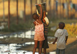 Children help each other to carry a bucket filled with water in Harare, Sept. 8, 2019. Shortages of electricity, water, fuel and cash are the latest symptoms of Zimbabwe's economic decline that began in 2000 when Mugabe launched the seizures of farms owned by whites. (AP Photo/Tsvangirayi Mukwazhi, File)