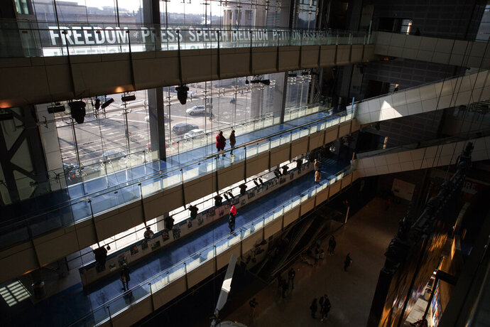 In this Friday, Dec. 20, 2019, photo, people visit the Newseum, in Washington. The Newseum will close the Pennsylvania Avenue location on Dec. 31, 2019. It attracted millions of visitors but lacked a solid financial plan to stay afloat. The mission of the Newseum is to increase public understanding of the importance of a free press and the First Amendment. (AP Photo/Jacquelyn Martin)