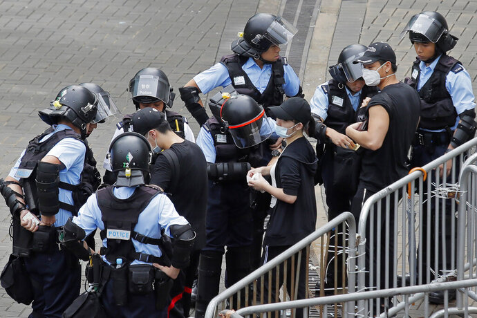Riot police check the bags of protesters outside the Legislative Council in Hong Kong, Thursday, June 13, 2019. After days of silence, Chinese state media is characterizing the largely peaceful demonstrations in Hong Kong as a