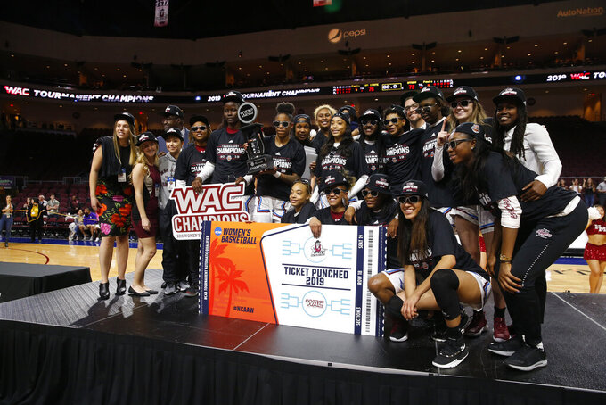 New Mexico State players and coaches pose with the trophy after defeating Texas-Rio Grande Valley 76-73 in double overtime during a NCAA college basketball Western Athletic Conference Women's Tournament championship game Saturday, March 16, 2019, in Las Vegas. (AP Photo/Steve Marcus)