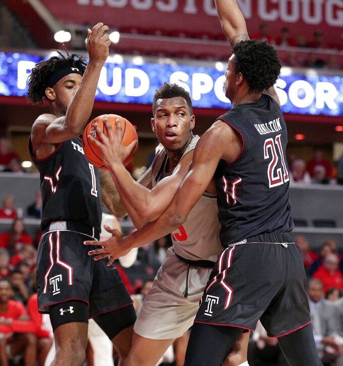 Houston forward Fabian White Jr., center, looks to pass the ball under pressure from Temple guard Quinton Rose (1) and forward Justyn Hamilton (21) during the first half of an NCAA college basketball game Thursday, Jan. 31, 2019, in Houston. (AP Photo/Michael Wyke)