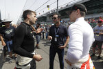 FILE - In this May 16, 2019, file photo, NASCAR driver Jimmie Johnson, center, talks with Will Power, left, of Australia, and Josef Newgarden during practice for the Indianapolis 500 IndyCar auto race at Indianapolis Motor Speedway in Indianapolis. NASCAR seven-time champion Jimmie Johnson will test an Indy car next week on the road course at Indianapolis Motor Speedway. He's long said he is open to racing in the series but did not want to compete on ovals out of safety concerns. On Friday, July 3, 2020, he indicated recent safety improvements have softened his stance and the Indianapolis 500 is not entirely out of the picture(AP Photo/Darron Cummings)