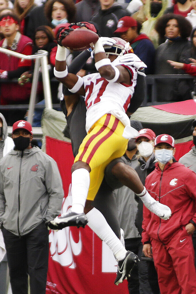 Southern California safety Calen Bullock, front, intercepts a pass intended for Washington State wide receiver Calvin Jackson Jr. during the second half of an NCAA college football game, Saturday, Sept. 18, 2021, in Pullman, Wash. Southern California won 45-14. (AP Photo/Young Kwak)