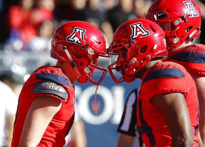 Arizona wide receiver Tony Ellison, left, celebrates with Khalil Tate (14) after scoring a touchdown against Arizona State in the first half during an NCAA college football game, Saturday, Nov. 24, 2018, in Tucson, Ariz. (AP Photo/Rick Scuteri)