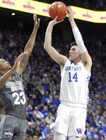 Kentucky's Tyler Herro (14) shoots while defended by Mississippi State's Tyson Carter (23) during the first half of an NCAA college basketball game in Lexington, Ky., Tuesday, Jan. 22, 2019. (AP Photo/James Crisp)