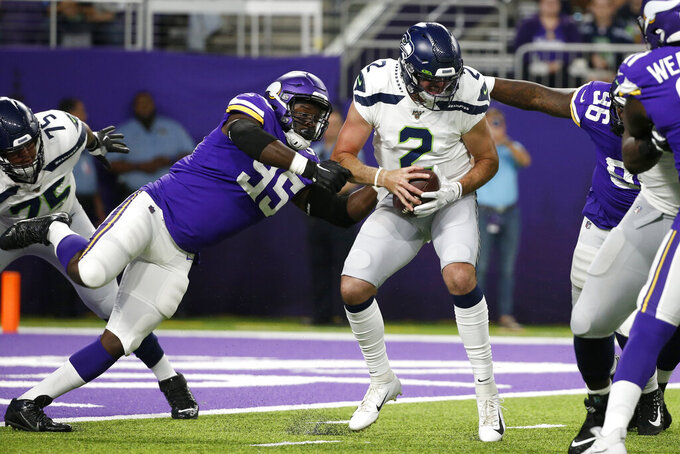 Seattle Seahawks quarterback Paxton Lynch (2) is sacked by Minnesota Vikings defensive end Ifeadi Odenigbo, left, during the first half of an NFL preseason football game, Sunday, Aug. 18, 2019, in Minneapolis. (AP Photo/Bruce Kluckhohn)