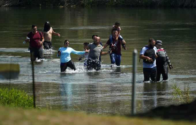 A group of migrants mainly from Venezuela wade through the Rio Grande as they cross the U.S.-Mexico border, Wednesday, June 16, 2021, in Del Rio, Texas. Record numbers of Venezuelans are crossing the U.S.-Mexico border as overall migration swells. (AP Photo/Eric Gay)