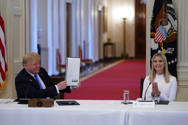 "FILE - In this June 26, 2020, file photo, Ivanka Trump, right, applauds as President Donald Trump holds an executive order that he signed during a meeting with the American Workforce Policy Advisory Board, in the East Room of the White House in Washington. A new White House-backed ad campaign aims to encourage people who are unemployed or unhappy in their jobs or careers to ""find something new."" (AP Photo/Evan Vucci, File)"