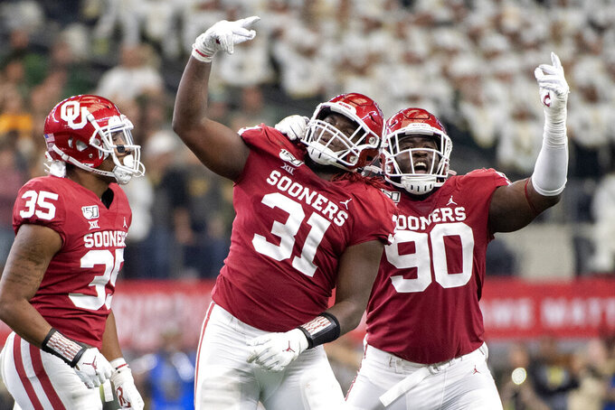 Oklahoma defensive tackle Jalen Redmond (31), defensive lineman Neville Gallimore (90) and linebacker Nik Bonitto (35) celebrate Redmond's sack of Baylor quarterback Gerry Bohanon during the second half of an NCAA college football game for the Big 12 Conference championship, Saturday, Dec. 7, 2019, in Arlington, Texas. (AP Photo/Jeffrey McWhorter)