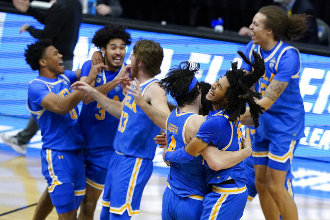 FILE - UCLA guard Tyger Campbell, right, celebrates with teammate guard Jaime Jaquez Jr. (4) after an Elite 8 game against Michigan in the NCAA men's college basketball tournament at Lucas Oil Stadium, in Indianapolis, in this Wednesday, March 31, 2021, file photo. UCLA won 51-49. UCLA is an overwhelming favorite to win the Pac-12 after reaching the Final Four last season. The Bruins' men's basketball team received 32 votes from 34 media members who cover the league in the preseason poll. (AP Photo/Darron Cummings, File)