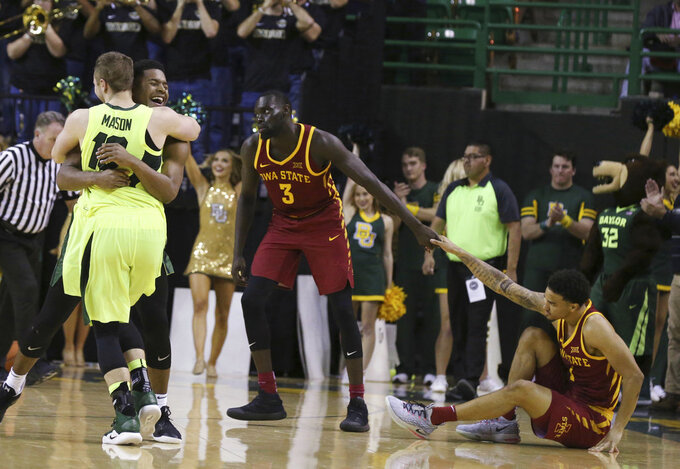 Baylor guard Makai Mason (10) hugs guard Jared Butler while Iowa State guard Marial Shayok (3) helps up guard Nick Weiler-Babb, right, following an NCAA college basketball game Tuesday, Jan. 8, 2019, in Waco, Texas. Baylor won 73-70. (AP Photo/Rod Aydelotte)