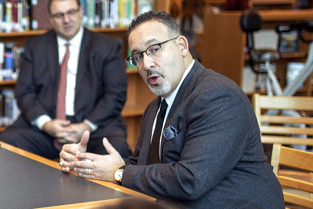 FILE - In this Jan. 28, 2020 file photo, Connecticut State Commissioner of Education Miguel Cardona speaks with Berlin High School students while on a tour of the school. President-elect Joe Biden has chosen the education commissioner for Connecticut and a former public school teacher to serve as education secretary.  (Devin Leith-Yessian/Berlin Citizen/Record-Journal via AP)