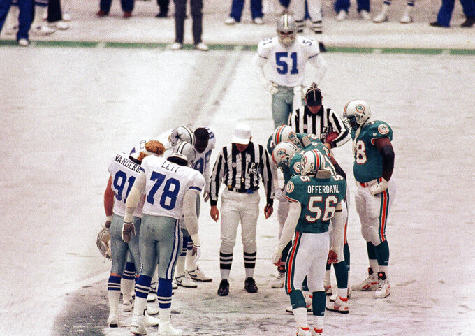 FILE - In this Nov. 25, 1993 file photo, The Dallas Cowboys and Miami Dolphins meet on the icy field of Texas Stadium for an NFL football game on Thanksgiving Day in Irving, Texas. Leon Lett learned in the Super Bowl never to celebrate too soon. His blunder the following Thanksgiving night schooled the entire Dallas Cowboys in that same painful lesson. (AP Photo/Glenn James, File)