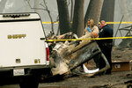 A sheriff's deputy recovers the remains of a Camp Fire victim from an overturned car in Paradise, Calif., on Thursday, Nov. 15, 2018. (AP Photo/Noah Berger)