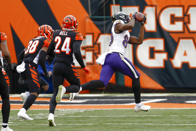 Baltimore Ravens wide receiver Miles Boykin (80) makes a catch past Cincinnati Bengals strong safety Vonn Bell (24) and takes it in for a touchdown during the first half of an NFL football game, Sunday, Jan. 3, 2021, in Cincinnati. (AP Photo/Aaron Doster)