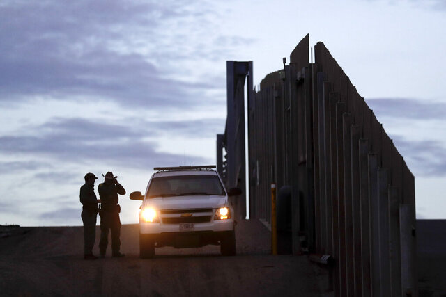 FILE - In this Nov. 21, 2018 file photo, United States Border Patrol agents stand by a vehicle near one of the border walls separating Tijuana, Mexico and San Diego, in San Diego. As of this week, the ACLU has filed nearly 400 lawsuits and other legal actions against the Trump administration, some meeting with setbacks but many resulting in important victories. Of the lawsuits, 174 have dealt with immigrant rights, targeting the family separation policy, detention and deportation practices, and the administration's repeated attempts to make it harder to seek asylum at the U.S.-Mexico border.  (AP Photo/Gregory Bull, File)