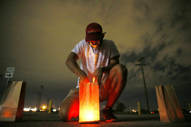 Adrian Arvizo lights luminarias for the luminaria remembrance drive-thru to honor the one-year mark of Aug. 3, 2019, at Ascarate Park Sunday, Aug. 2, 2020,  in El Paso, Texas.  (Briana Sanchez/The El Paso Times via AP)