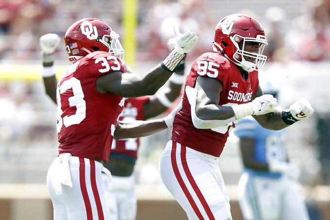 Oklahoma linebacker Marcus Stripling, left, and defensive lineman Isaiah Thomas celebrate after a sack against Tulane during NCAA college football game in Norman, Okla. on Saturday, Sept. 4, 2021. (Ian Maule/Tulsa World via AP)