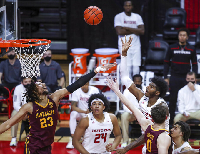 Rutgers center Myles Johnson (15) shoots as Minnesota forward Brandon Johnson (23) and center Liam Robbins (0) defend during the second half of an NCAA college basketball game Thursday, Feb. 4, 2021, in Piscataway, N.J. (Andrew Mills/NJ Advance Media via AP)