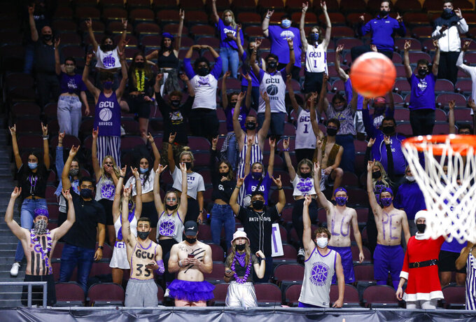 Grand Canyon fans raise their hands during a free throw attempt in the second half of the team's NCAA college basketball game against New Mexico State for the championship of the Western Athletic Conference men's tournament Saturday, March 13, 2021, in Las Vegas. (AP Photo/Chase Stevens)
