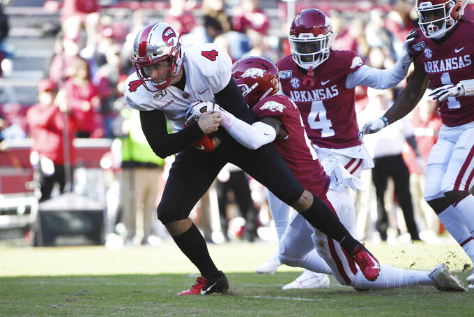 Western Kentucky quarterback Ty Storey is tackled by Arkansas defender Montaric Brown as he runs the ball down to the goal line during the second half of an NCAA college football game, Saturday, Nov. 9, 2019 in Fayetteville, Ark. (AP Photo/Michael Woods)