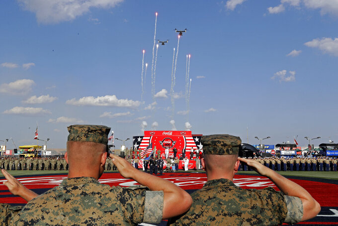 Soldiers salute during the national anthem before a NASCAR Cup Series auto race at Charlotte Motor Speedway in Concord, N.C., Sunday, May 26, 2019. (AP Photo/Chuck Burton)