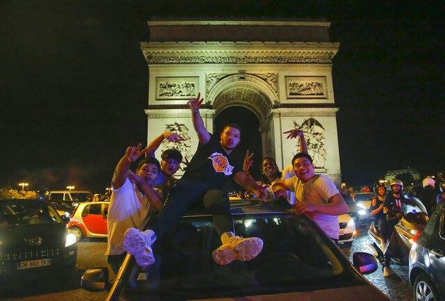 Supporters of the Paris Saint Germain soccer team celebrates on the Champs Elysee in Paris, Tuesday, Aug. 18, 2020 after his team won 3-0 against RB Leipzig. (AP Photo/Michel Euler)