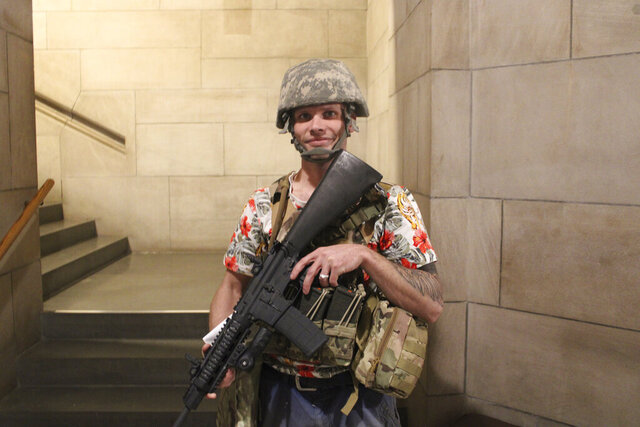 CORRECTS SOURCE TO NET NEWSNEBRASKA - This Feb. 21, 2020 photo provided by NET NewsNebraska shows Brett Hendrix, who brought an assault rifle to the Nebraska State Capitol in Lincoln to demonstrate his Second Amendment rights. Some Nebraska lawmakers expressed shock and outrage Monday, Feb. 24, 2020 that gun owners were allowed to bring loaded, semi-automatic rifles into the state Capitol to protest bills that would have imposed new restrictions on gun ownership. (Fred Knapp/NET NewsNebraska via AP)
