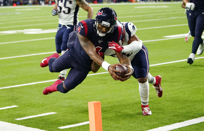 FILE - In this Dec. 1, 2019, file photo, Houston Texans quarterback Deshaun Watson (4) dives past New England Patriots outside linebacker Elandon Roberts (52) to score a touchdown during the second half of an NFL football game in Houston. The photo was part of a series of images by photographer David J. Phillip which won the Thomas V. diLustro best portfolio award for 2019 given out by the Associated Press Sports Editors during their annual winter meeting in St. Petersburg, Fla. (AP Photo/David J. Phillip, File)