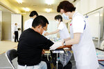 A nurse takes a blood sample from a resident in Natori, Miyagi prefecture, northern Japan, Monday, June 1, 2020. The Japanese Health Ministry began testing around 10,000 people for coronavirus antibodies on Monday to better understand its spread. (Kyodo News via AP)