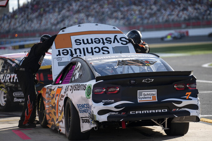 Crew members look under the hood of Corey LaJoie's (7) car during a NASCAR Cup Series auto racing race at Charlotte Motor Speedway, Sunday, Oct. 10, 2021, in Concord, N.C. (AP Photo/Matt Kelley)