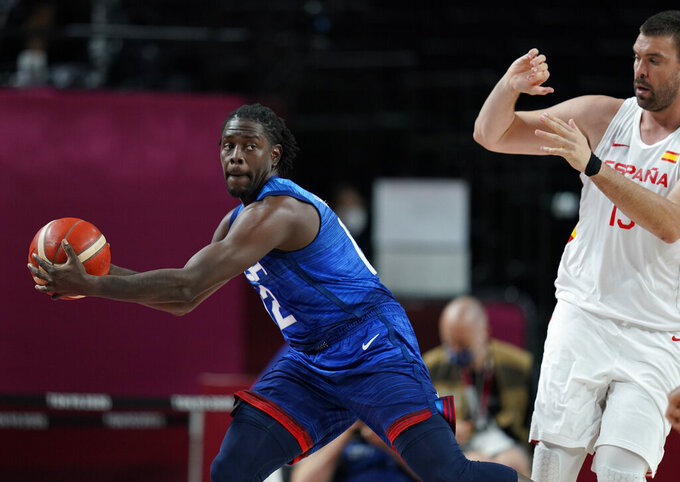 United States' Jrue Holiday (12), left, grabs the ball in front of Spain's Marc Gasol (13), right, during men's basketball quarterfinal game at the 2020 Summer Olympics, Tuesday, Aug. 3, 2021, in Saitama, Japan. (AP Photo/Charlie Neibergall)
