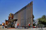 Government contractors erect a section of Pentagon-funded border wall along the Colorado River, Tuesday, Sept. 10, 2019 in Yuma, Ariz. The 30-foot high wall replaces a five-mile section of Normandy barrier and post-n-beam fencing along the the International border that separates Mexico and the United States. Construction began as federal officials revealed a list of Defense Department projects to be cut to pay for President Donald Trump's wall. (AP Photo/Matt York)