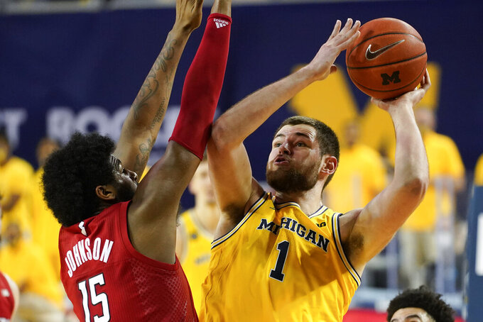 Michigan Wolverines center Hunter Dickinson (1) shoots on Rutgers center Myles Johnson (15) in the first half of an NCAA college basketball game in Ann Arbor, Mich., Thursday, Feb. 18, 2021. (AP Photo/Paul Sancya)
