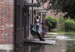 Residents at Trent Court Apartments wait out the weather as rising waters get closer to their doors in New Bern, N.C. Thursday, Sept. 13, 2018. Hurricane Florence already has inundated coastal streets with ocean water and left tens of thousands without power, and more is to come.  (Gray Whitley/Sun Journal via AP)
