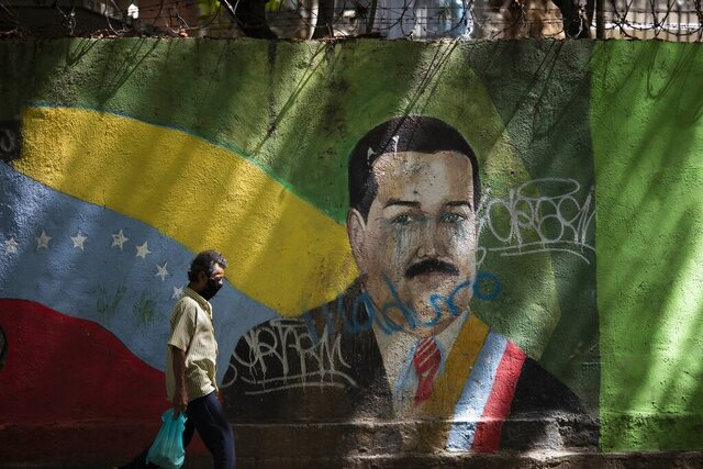 A man wearing a face mask amid the COVID-19 pandemic passes a mural of Venezuelan President Nicolas Maduro in Caracas, Venezuela, Wednesday, July 22, 2020. Analysts say that in recent months the pandemic has helped suck away the opposition's scanty momentum and bolster Maduro's already strong hand. (AP Photo/Ariana Cubillos)