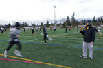 Brant McAdams, right, football coach at Pacific Lutheran, uses an electronic push-button whistle to guide players as they run socially distanced drills during practice Tuesday, Feb. 2, 2021, on campus in Tacoma, Wash. The whistle, which is more hygienic than traditional ones that are blown, is one of many measures taken by PLU and other schools to try and prevent the spread of COVID-19. For all the attention heaped on the FBS level of college football last fall as it tried to play, it will not be the only college football during the 2020-21 sports calendar as a handful of NCAA Division III and NAIA programs begin some form of a winter/spring season Saturday, Feb. 6. (AP Photo/Ted S. Warren)