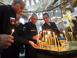Navy sailors light candles during a religion service to commemorate the crew members that were killed on one of the Russian navy's deep-sea research submersibles at Kronshtadt Navy Cathedral outside St.Petersburg, Russia, Thursday, July 4, 2019. Some crew members survived a fire that killed 14 sailors on one of the Russian navy's deep-sea submersibles, Russia's defense minister said Wednesday without specifying the number of survivors from the blaze. (AP Photo/Dmitri Lovetsky)