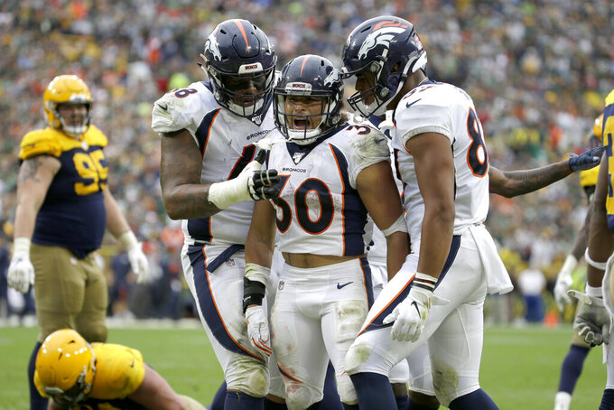 Denver Broncos running back Phillip Lindsay (30) is congratulated by teammates Elijah Wilkinson, left, and Noah Fant, right, after scoring during the second half of an NFL football game against the Green Bay Packers Sunday, Sept. 22, 2019, in Green Bay, Wis. (AP Photo/Mike Roemer)