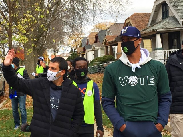 Milwaukee Bucks senior vice president Alex Lasry, left, and guard George Hill walk through a Milwaukee neighborhood during a voter canvassing effort Saturday, Oct. 24, 2020. Hill and Lasry joined volunteers from the Milwaukee-based Common Ground organization to remind local residents to vote.  (AP Photo/Steve Megargee)