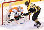 Philadelphia Flyers goaltender Carter Hart (79) makes a save against Boston Bruins left wing Jake DeBrusk (74) during first-period NHL hockey playoff action in Toronto, Sunday, Aug. 2, 2020. (Frank Gunn/The Canadian Press via AP)