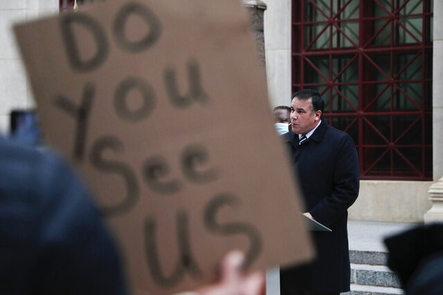 A demonstrator holds up a sign as Columbus Mayor Andrew J. Ginther speaks during a press conference following a fatal police shooting on Tuesday, Dec. 22, 2020 at City Hall in Columbus, Ohio. A police officer who shot and killed a Black man holding a cell phone in Ohio's capital city early Tuesday did not activate his body camera beforehand, and dash cameras on the officers' cruiser were also not activated, city officials said. (Joshua A. Bickel/The Columbus Dispatch via AP)