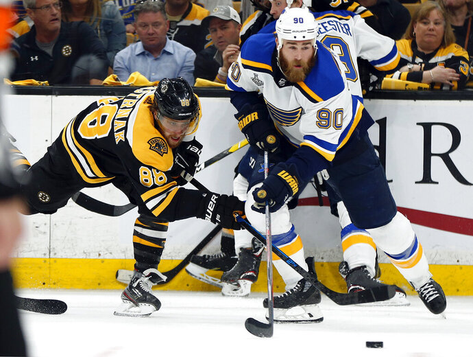 St. Louis Blues' Ryan O'Reilly (90) moves the puck away from Boston Bruins' David Pastrnak, left, of the Czech Republic, during the second period in Game 7 of the NHL hockey Stanley Cup Final, Wednesday, June 12, 2019, in Boston. (AP Photo/Michael Dwyer)