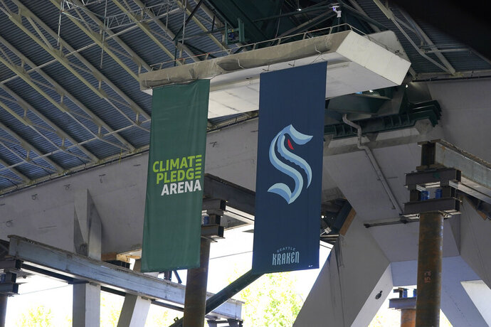 Flags for the Seattle Kraken NHL hockey team and the Amazon-sponsored Climate Pledge Arena hang in the rafters Tuesday, Sept. 1, 2020, as work continues in Seattle on the home of the Seattle Kraken NHL hockey team. Sometime in the late summer or early fall of 2021, the Kraken will open the new facility -- at a cost that will likely total $1 billion by the time it's done -- and become the NHL's 32nd franchise. (AP Photo/Ted S. Warren)