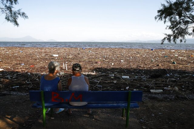 Debris covers the beach after a storm from the opposite island of Evia, as an elderly couple sits on a bench in Chalkoutsi village, about 60 kilometres north of Athens, Monday, Aug. 10, 2020. Seven people, including an elderly couple and an 8-month-old baby, have been found dead as a storm hit the Greek island of Evia, authorities said Sunday. One person was still missing and dozens of others were trapped by floodwaters in their homes and cars. (AP Photo/Thanassis Stavrakis)